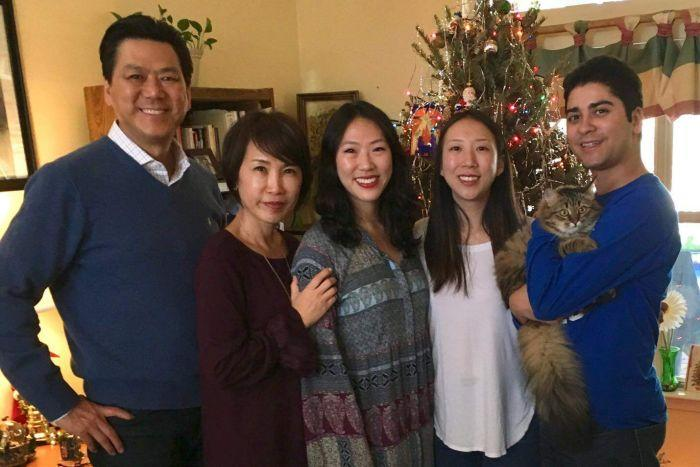 Calvin Chin with his family in front of a Christmas tree.