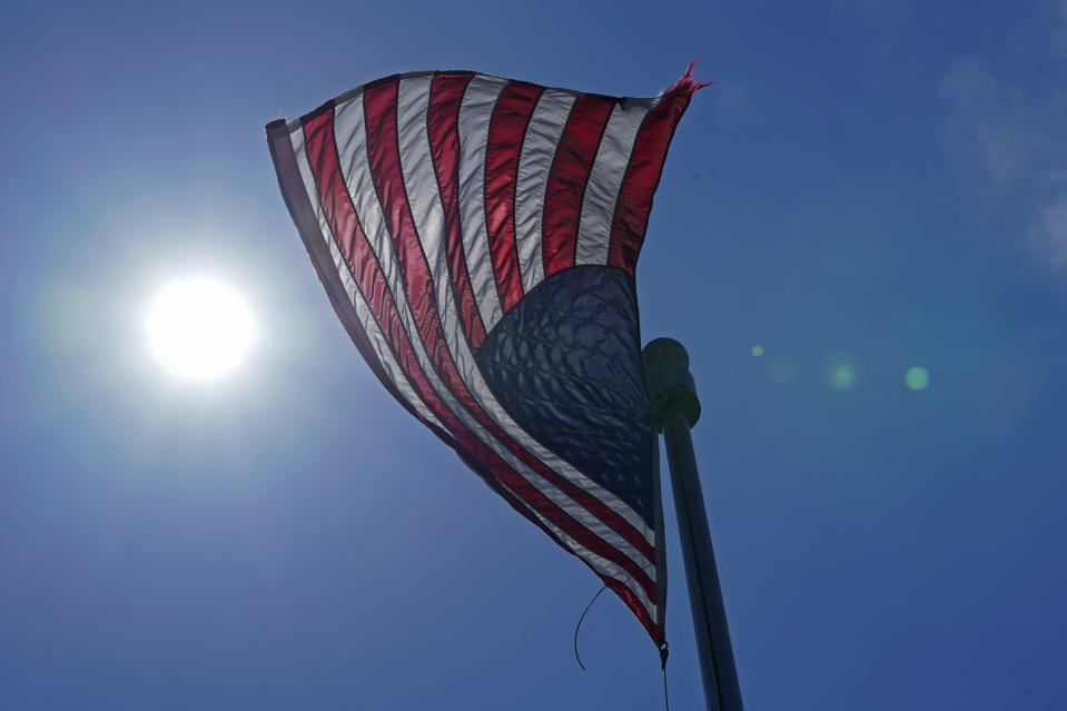 In this Wednesday, June 30, 2021 photo, a U.S. flag flies with the sun in the background in downtown Seattle. As outlandish as the killer heat wave that struck the Pacific Northwest and other areas was, it fit into a decades-long pattern of uneven summer warming in the United States, climate scientists say and federal weather records show. (AP Photo/Ted S. Warren, File)