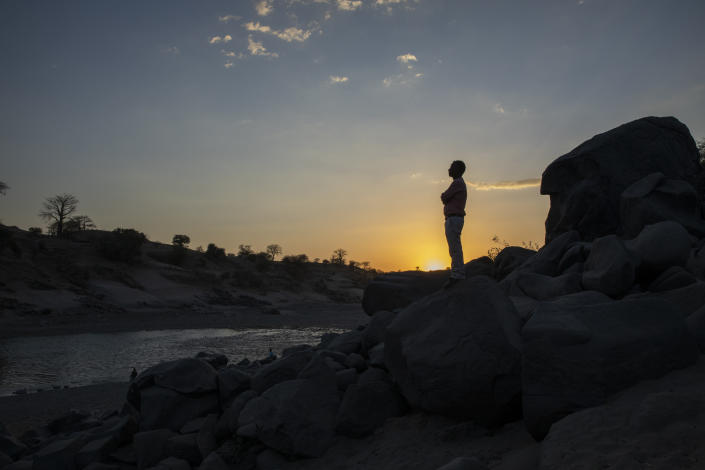 Surgeon and doctor-turned-refugee, Dr. Tewodros Tefera, stands at the Tezeke River crossing in Hamdayet, Sudan, on March 16, 2021. At left across the river is Ethiopia. He plans to continue his work in Sudan. The high-rise buildings of his city in Tigray, Humera, can be seen on the horizon. He could walk home, but he's not sure he will ever go there again. (AP Photo/Nariman El-Mofty)