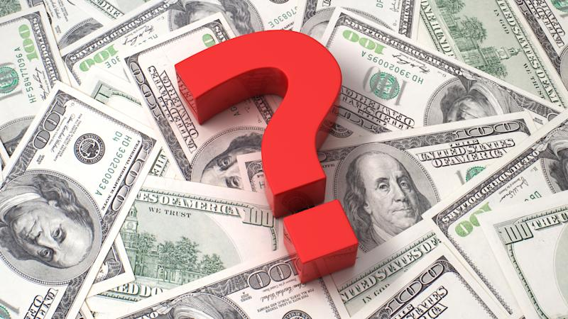 A red question mark on top of a pile of one hundred dollar bills.