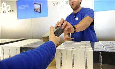 An Apple employee hands out an iPhone 5 at an Apple Store in San Francisco