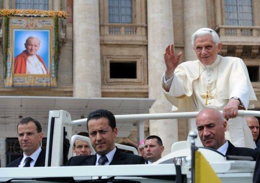 Pope Benedict XVI (R) waves as he stands in his popemobile with his butler Paolo Gabriele (C)