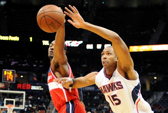 Atlanta Hawks' Al Horford (15) battles for the rebound with Washington Wizards' John Wall, left, in the first half of an NBA basketball game on Friday, Dec. 13, 2013, in Atlanta. (AP Photo/David Tulis)