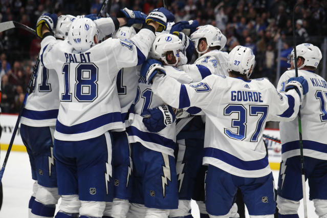 Tampa Bay Lightning right wing Nikita Kucherov is mobbed by teammates after scoring the winning goal in overtime of an NHL hockey game against the Colorado Avalanche Monday, Feb. 17, 2020, in Denver. The Lightning won 4-3. (AP Photo/David Zalubowski)