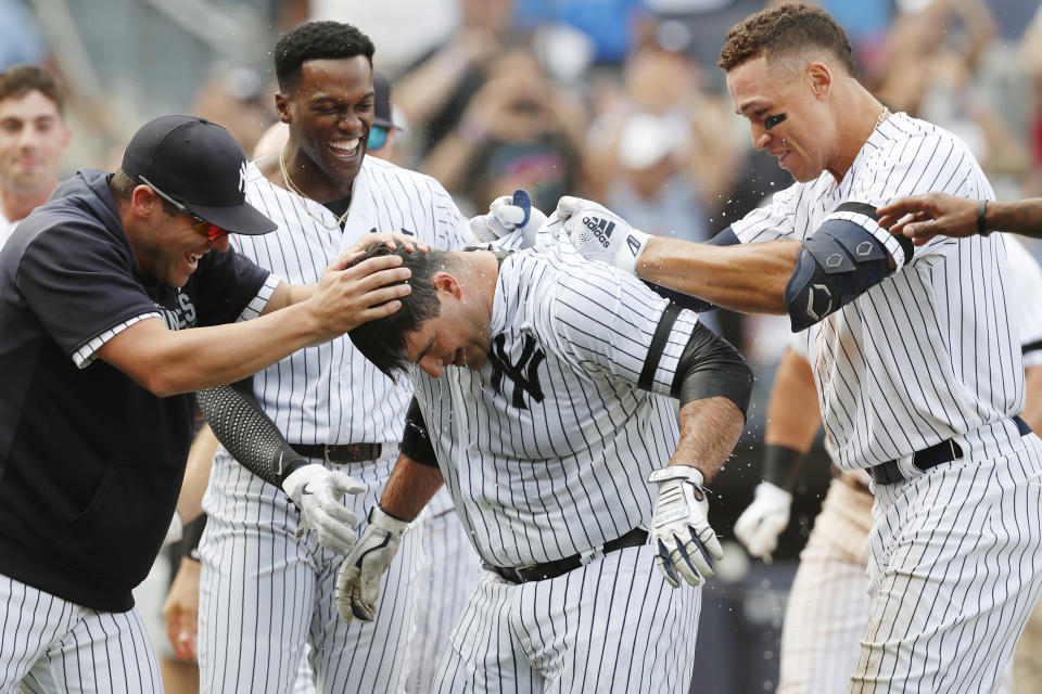 The New York Yankees celebrate with Mike Ford, center, after he hit a walk-off, pinch-hit, solo home run during a baseball game against the Oakland Athletics, Sunday, Sept. 1, 2019, in New York. The Yankees won 5-4. (AP Photo/Kathy Willens)