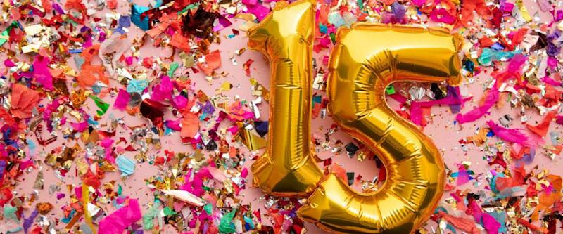 Number 15 gold birthday celebration balloon on a confetti glitter background