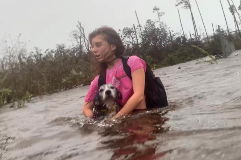 Julia Aylen wades through waist deep water carrying her pet dog as she is rescued from her flooded home during Hurricane Dorian in Freeport, Bahamas, Sept. 3, 2019. (Photo: Tim Aylen/AP)
