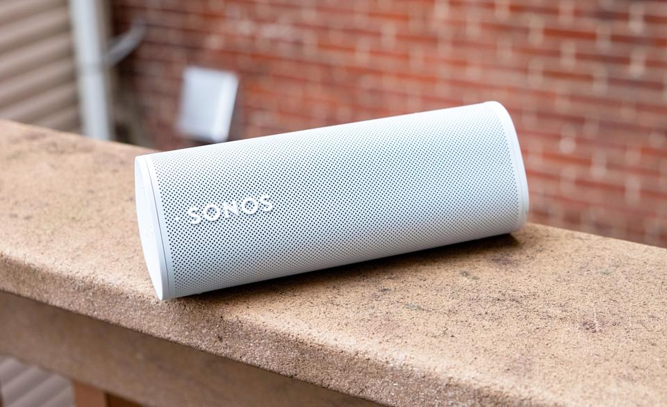 A white Sonos Roam speaker sitting on the railing of a balcony with a brick wall in the background.