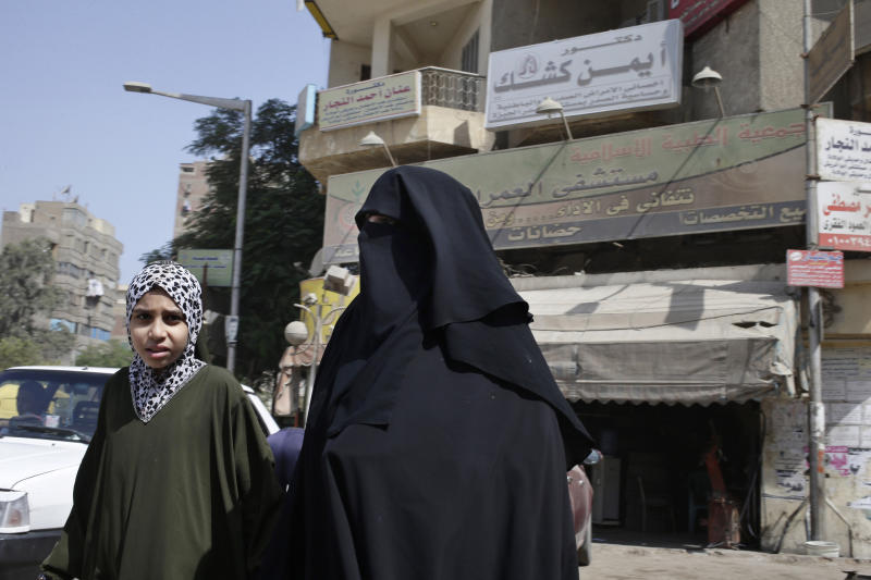 In this Saturday, Sept. 21, 2013 photo, an Egyptian woman and her daughter walk in front of Al-Omraniyah hospital, run by the Muslim Brotherhood's Islamic Medical Association, in Cairo, Egypt. An Egyptian court ordered a ban of the Muslim Brotherhood and confiscation of its assets Monday, Sept. 23, 2013, opening the door for authorities to dramatically accelerate a widescale crackdown. Egypt's military-backed leaders have gone beyond arresting the group's leaders to try to strike a more longterm blow, targeting its extensive network of schools, hospitals, mosques and other social institutions that made it the country's strongest political power. (AP Photo/Hassan Ammar)