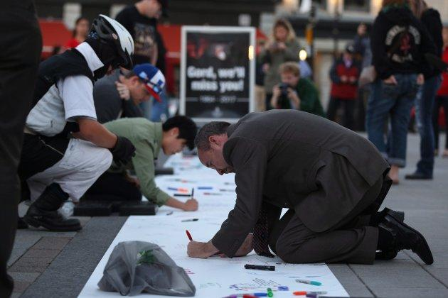 Kingston's Mayor Bryan Paterson writes messages for Gord Downie of the Tragically Hip on a banner in downtown Kingston, Ont., on Wednesday.