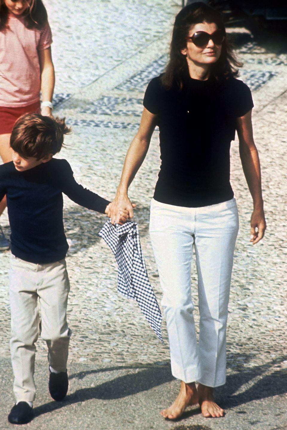 <p>In an iconic casual look, Kennedy-Onassis goes barefoot in Rome in 1968 in cropped white denim and a navy tee. Her signature oversized shades were also on display.</p>