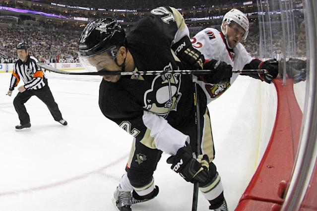 Pittsburgh Penguins' Jarome Iginla (12) gets a stick in the face during a struggle in the corner with Ottawa Senators' Erik Condra (22) in the second period of Game 2 of an NHL hockey Stanley Cup second-round playoff series, in Pittsburgh on Friday, May 17, 2013.(AP Photo/Gene J. Puskar)