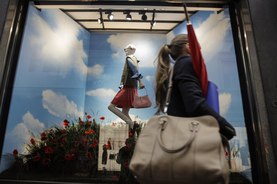 A woman walks past the Gucci store window at the Via Montenapoleone fashion district, during the Milan's fashion week in Milan, Italy, Friday, Sept. 25, 2020. (AP Photo/Luca Bruno)