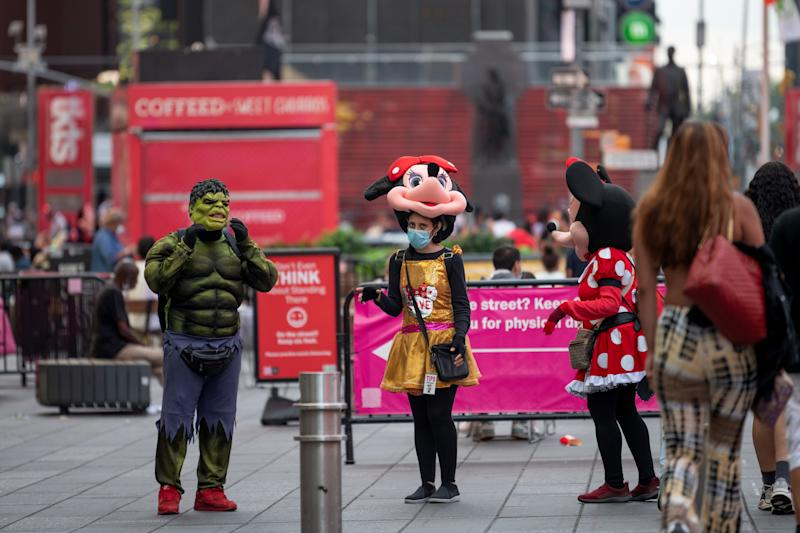 NEW YORK, NEW YORK - JULY 07: A woman wearing a Minnie Mouse costume wears a mask in Times Square as the city moves into Phase 3 of re-opening following restrictions imposed to curb the coronavirus pandemic on July 7, 2020 in New York City. Phase 3 permits the reopening of nail and tanning salons, tattoo parlors, spas and massages, dog runs and numerous other outdoor activities. Phase 3 is the third of four-phased stages designated by the state. (Photo by Alexi Rosenfeld/Getty Images)