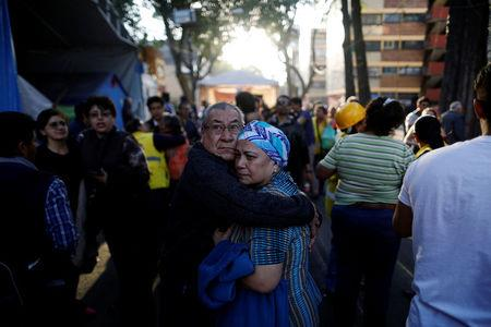 People react after an earthquake shook buildings in Mexico City