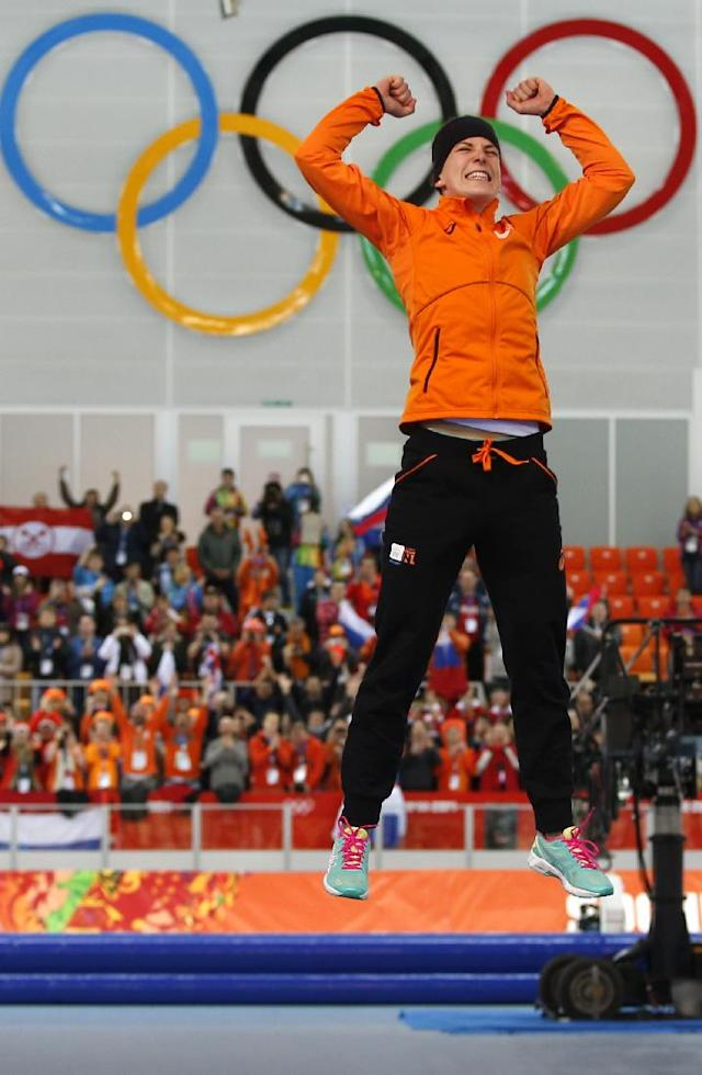 Ireen Wust of the Netherlands celebrates winning gold during the flower ceremony for the women's 3,000-meter speedskating race at the Adler Arena Skating Center during the 2014 Winter Olympics, Sunday, Feb. 9, 2014, in Sochi, Russia