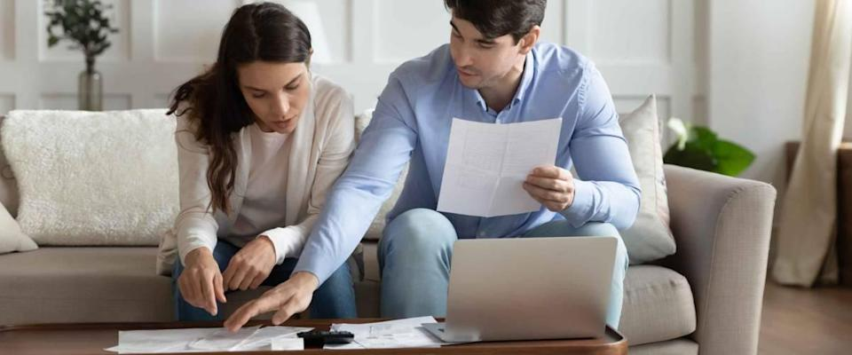 Concentrated attentive millennial spouses sitting on couch at home discussing whether to refinance their mortgage.