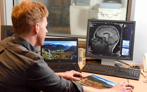 Dr Andy Myers looking at brain scans - Credit: The National Trust