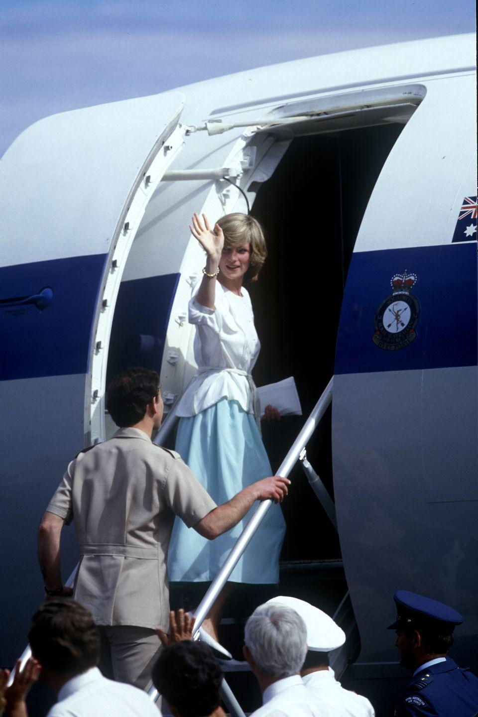 <p>Diana boards a plane in a white blouse and blue skirt as she leaves Alice Springs. </p>