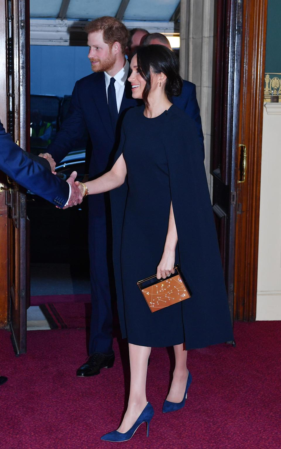 <p>The cape dress, which retails for approximately $2,300 CAD isn't your traditional choice for a royal — but it worked perfectly for the former actress. She combined the navy look with matching Manolo Blahnik pumps and a Naeem Khan zodiac-inspired clutch, which retails for about $1,890 CAD. </p>