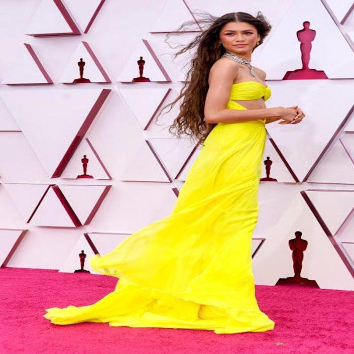 Zendaya poses on the Oscars red carpet in a brightly-colored strapless gown