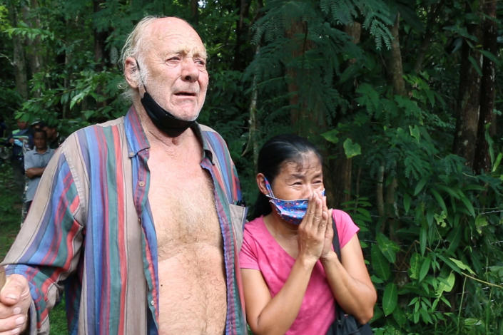 Barry Leonard Weller is reunited with his Thai partner, Tawee Chaisanrit, after he was rescued from the jungle, in Thailand's northeastern Khon Kaen province, Friday, Sept. 3, 2021. A 72-year-old British man has been found safe three days after disappearing in a thick jungle in northeastern Thailand while going to visit friends on a motorbike. A member of a local volunteer team that helped rescue him said a hunter came across Barry Leonard Weller in a remote forest in Khon Kaen province. He was asleep on a rock formation after climbing it to try to see a route out. (AP Photo/Tanadon Sribura)