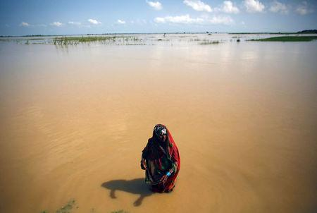 A flood victim washes herself at the flood affected area in Saptari District