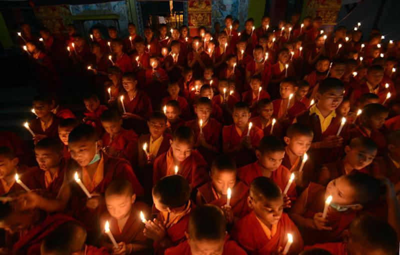 Novice Buddhist monks light candles in remembrance of an Indian woman who died after being gang raped in a moving bus, in Bodhgaya, India, Sunday, Dec. 30, 2012. The young woman was cremated Sunday amid an outpouring of anger and grief by millions across the country demanding greater protection for women from sexual violence. (AP Photo/Manish Bhandari)