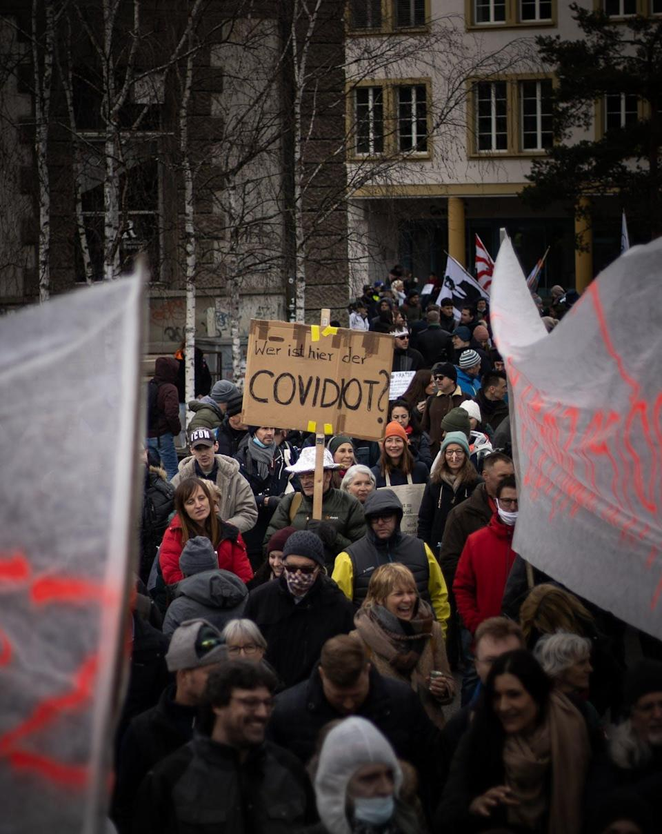 """<span class=""""caption"""">Man holds sign reading 'wer ist hier der COVIDIOT' which means 'who is the COVIDIOT here?' at a protest against pandemic restrictions in March, 2021. </span> <span class=""""attribution""""><span class=""""source"""">(Kajetan Sumila/Unsplash)</span></span>"""