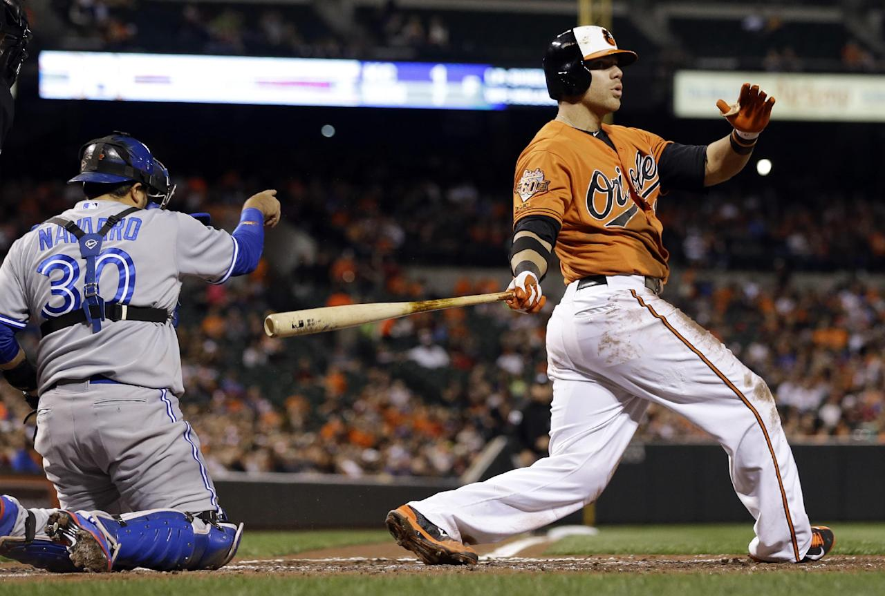 Baltimore Orioles' Chris Davis strikes out swinging in front of Toronto Blue Jays catcher Dioner Navarro in the third inning of a baseball game, Saturday, April 12, 2014, in Baltimore. (AP Photo/Patrick Semansky)