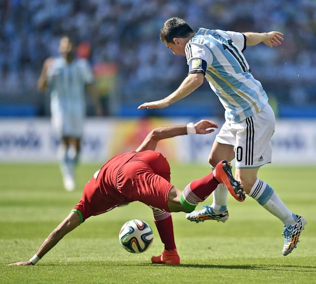 Argentina's Lionel Messi tries to get the ball away from Iran's Mehrdad Pooladi during the group F World Cup soccer match between Argentina and Iran at the Mineirao Stadium in Belo Horizonte, Brazil, Saturday, June 21, 2014. (AP Photo/Martin Meissner)