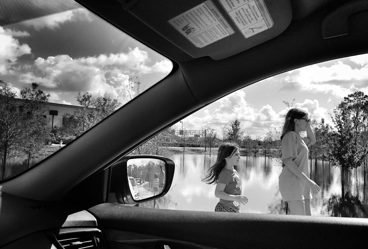 A mother and her daughter walk back to their car while waiting in a line that extended miles at one of the few gas stations open after Hurricane Irma in Fort Myers, Fla. (Photo: Holly Bailey/Yahoo News)