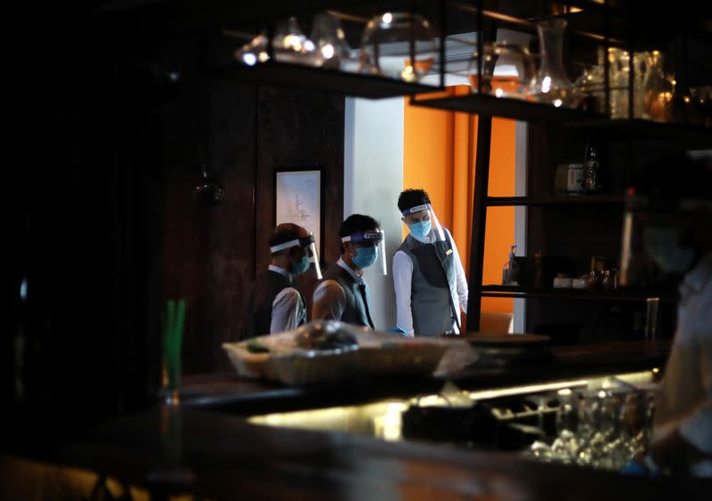 Servers wearing protective face shields are seen at a restaurant as India eases lockdown restrictions that were imposed to slow the spread of the coronavirus disease (COVID-19), in New Delhi