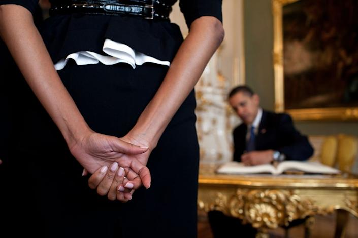 """First Lady Michelle Obama waits as the President signs the guestbook upon their arrival at Prague Castle in the Czech Republic, April 5, 2009. (Pete Souza / The White House) <br> <br> <a href=""""http://lightbox.time.com/2012/10/08/pete-souza-portrait-of-a-presidency/#1"""" rel=""""nofollow noopener"""" target=""""_blank"""" data-ylk=""""slk:Click here to see the full collection at TIME.com"""" class=""""link rapid-noclick-resp"""">Click here to see the full collection at TIME.com</a>"""