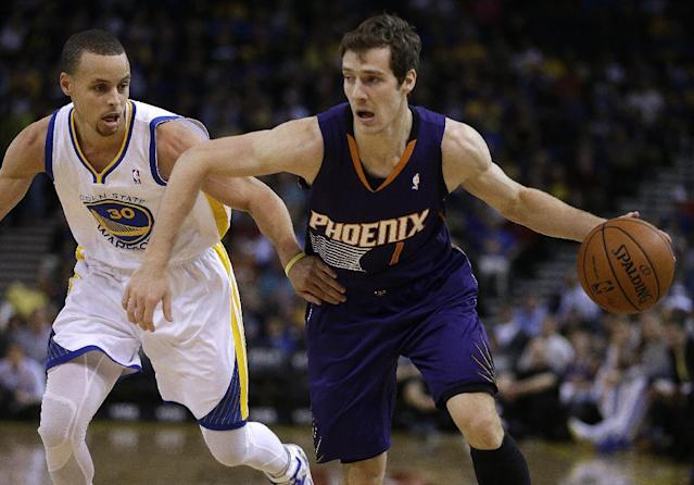 Phoenix Suns' Goran Dragic, right, drives the ball past Golden State Warriors' Stephen Curry (30) during the first half of an NBA basketball game Sunday, March 9, 2014, in Oakland, Calif. (AP Photo/Ben Margot)