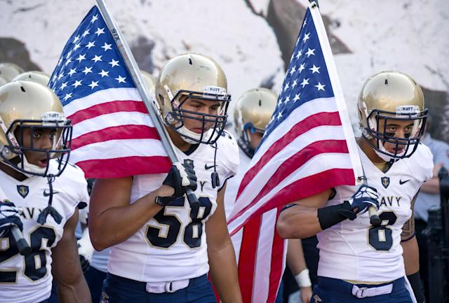 FILE - In this Sept. 7, 2013, file photo, from left, Navy's Marcus Thomas (26), Evan Palelei (58) and Wave Ryder (8) head onto the field at the start of an NCAA college football game against Indiana in Bloomington, Ind. The Defense Department said Tuesday, Oct. 1, 2013, that it has temporarily suspended all sports competitions at the service academies as a result of the partial government shutdown. The decision jeopardizes this weekend's football games , Air Force at Navy and Army at Boston College. (AP Photo/Doug McSchooler, File)