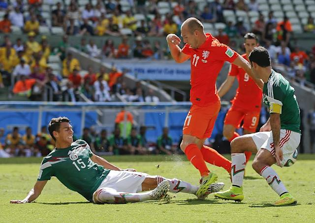 Mexico's Rafael Marquez, right, watches as teammate Hector Moreno slide tackles Netherlands' Arjen Robben during the World Cup round of 16 soccer match between the Netherlands and Mexico at the Arena Castelao in Fortaleza, Brazil, Sunday, June 29, 2014. (AP Photo/Eduardo Verdugo)