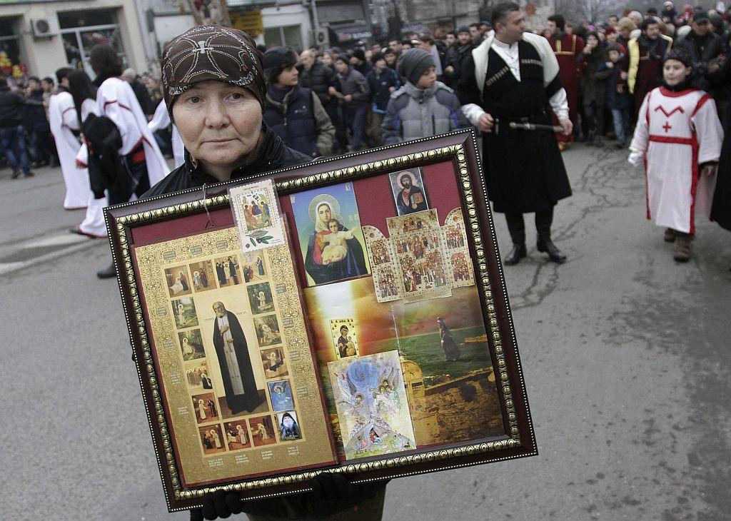 "GEORGIA: A woman carries a collection of religious icons as she takes part in ""Alilo"", a religious procession, to celebrate the Orthodox Christmas in Tbilisi January 7, 2013. Believers celebrate Christmas on January 7, according to the Julian calendar used by the country's Orthodox church."