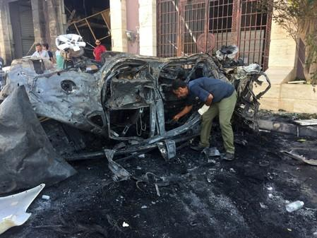 Security official inspects the site where a car bomb exploded in Benghazi