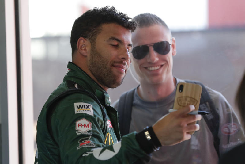 Bubba Wallace , left, takes a selfie photo with a fan during a NASCAR auto race practice at Daytona International Speedway, Saturday, Feb. 8, 2020, in Daytona Beach, Fla. (AP Photo/John Raoux)