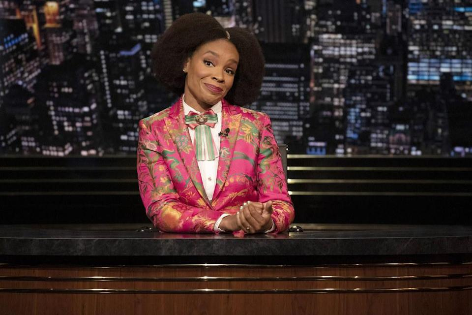 Amber Ruffin sits behind her late-night desk
