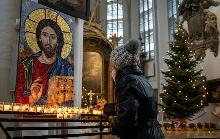 In Germany's capital Berlin, a worshipper lights a candle in St Mary's church ahead of an outdoor mass on Christmas Eve