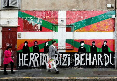 People walk in front of a wall graffiti with the Basque flag on a wall in the center of Bayonne
