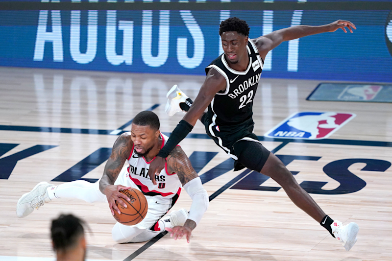 Portland's Damian Lillard chases the ball in front of Brooklyn's Caris LeVert during the teams' game Aug. 13 in Lake Buena Vista, Fla.