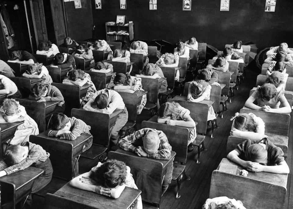 """<p>Elementary school students place their heads on their desk during the day's """"rest period.""""</p>"""