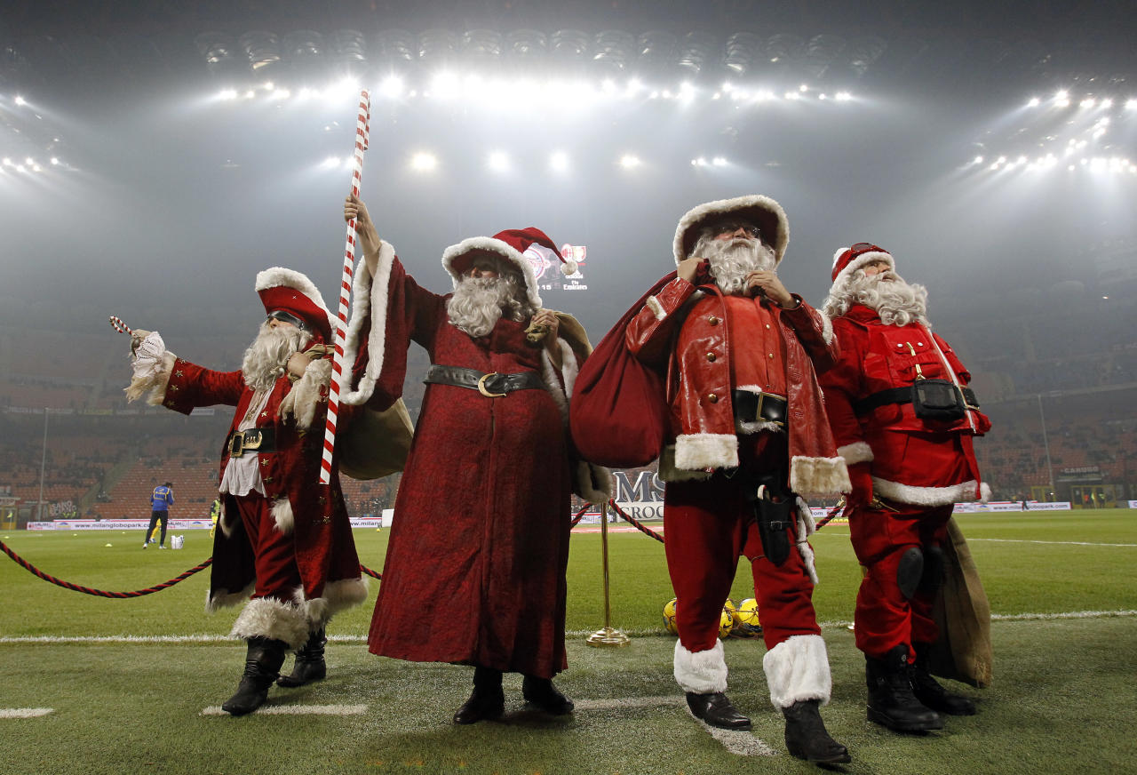 People wearing Santa Claus costumes stand on the field before the start of the Italian Serie A soccer match between AC Milan and Chievo at the San siro  stadium in Milan November 27, 2011. REUTERS/Alessandro Garofalo (ITALY - Tags: SPORT SOCCER TPX IMAGES OF THE DAY SOCIETY)