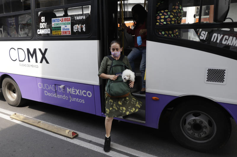 Public transport user from Mexico City, Mexico, on June 30, 2020 descending with her pet during the change from red to orange traffic light for COVID-19 in Mexico. (Photo by Gerardo Vieyra/NurPhoto via Getty Images)