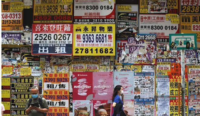 Pedestrians pass by a shuttered retail shop now covered in property agent contact numbers. Photo: K. Y. Cheng
