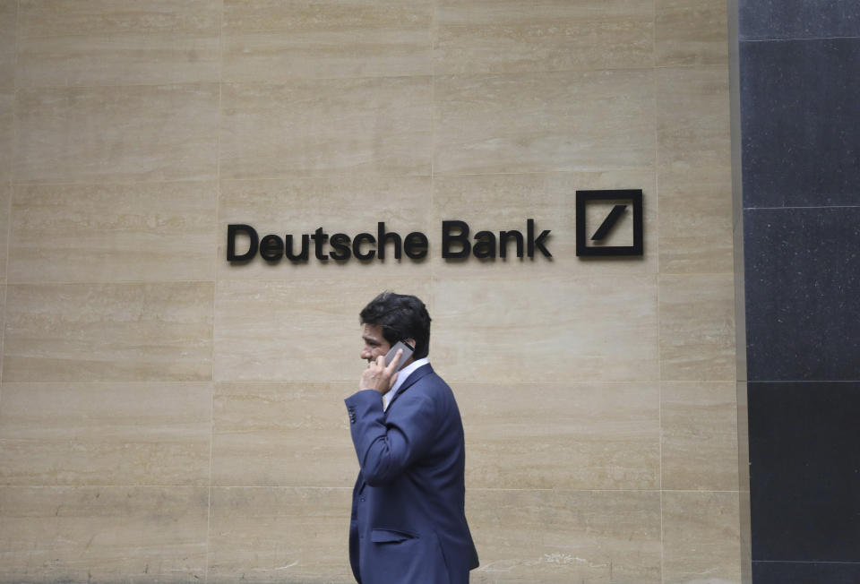 """A man walks past the Deutsche Bank sign in London, Monday, July, 8, 2019. Germany's struggling Deutsche Bank says it will cut 18,000 jobs by 2022,  saying it is going """"back to our roots"""" with a radical restructuring plan meant to focus the company on traditional strengths.(AP Photo/Natasha Livingstone)"""