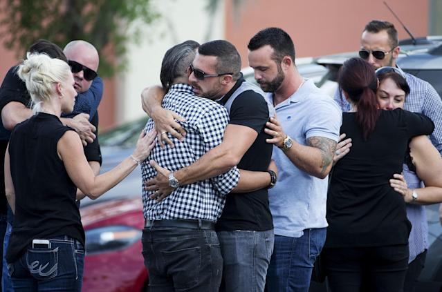 <p>Mourners embrace outside the visitation for a Pulse nightclub shooting victim, Javier Jorge-Reyes, in Orlando. (Photo: David Goldman/AP) </p>